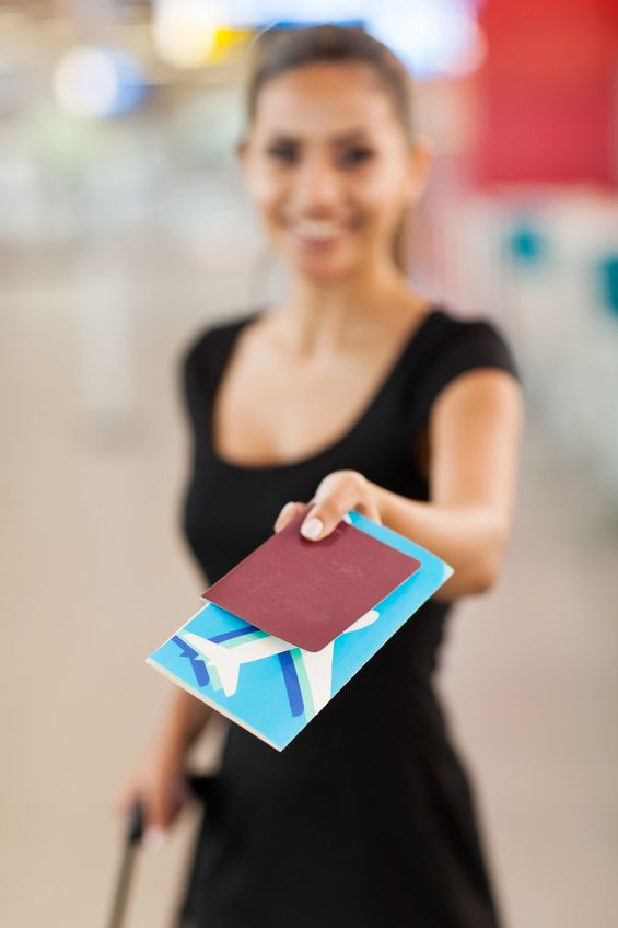 20659483 - smiling young businesswoman presenting air ticket and passport at airport